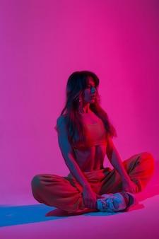 Profesjonalny trener młoda kobieta w modne ubrania robi joga w pokoju z jasnymi neonami. nowoczesna modna dziewczyna relaksuje się w studio w kolorze różowo-czerwonym. wysportowana dama. zdrowy tryb życia.