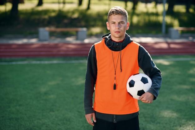 Profesjonalny trener piłki nożnej w pomarańczowej kamizelce i gwizdkiem na karku.