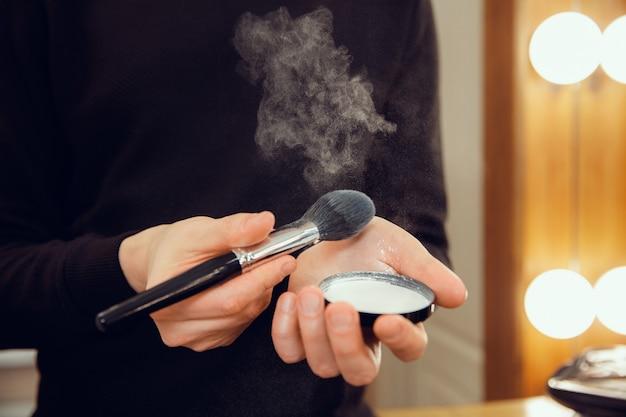 Profesjonalny wizażystka pracuje w salonie. mężczyzna w zawodzie żeńskim. pojęcie równości płci. męskie dłonie z zbliżenie pędzla