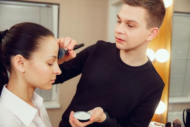 Profesjonalny wizażystka pracuje z piękną młodą kobietą. mężczyzna w zawodzie żeńskim. koncepcja równości płci