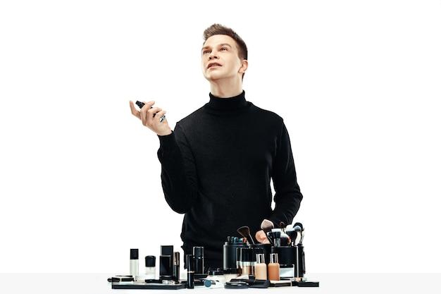 Profesjonalny wizażystka z narzędziami na białym tle na tle białego studia. mężczyzna w zawodzie żeńskim. koncepcja równości płci