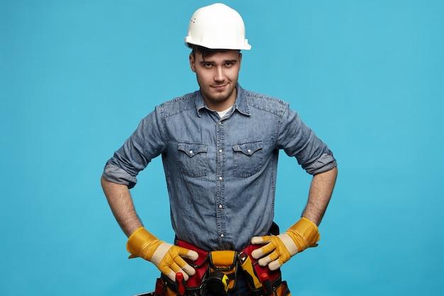 Profesjonalny wykwalifikowany młody elektryk w ochronnym hełmie i rękawiczkach, trzymając się za ręce w pasie