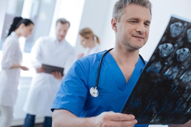 Profesjonalny wykwalifikowany uważny radiolog pracujący w laboratorium medycznym i badający skan tomograficzny, podczas gdy jego koledzy używają tabletu z tyłu