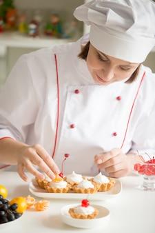 Profesjonalny żeński cukiernik dekorowanie mini tarta owocowa
