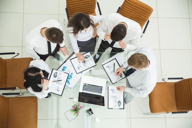 Profesjonalny zespół biznesowy opracowujący nową strategię finansową firmy w miejscu pracy w nowoczesnym biurze