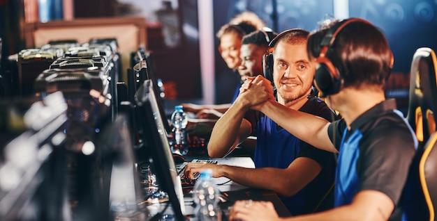Profesjonalny zespół cybersportowy. dwóch szczęśliwych graczy płci męskiej ściskających sobie dłonie, świętujących sukces podczas udziału w turnieju e-sportowym. konkurs gier wideo online