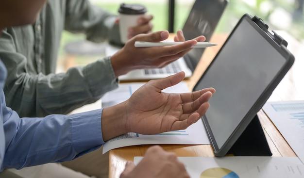 Profesjonalny zespół omawia informacje z tabletu.