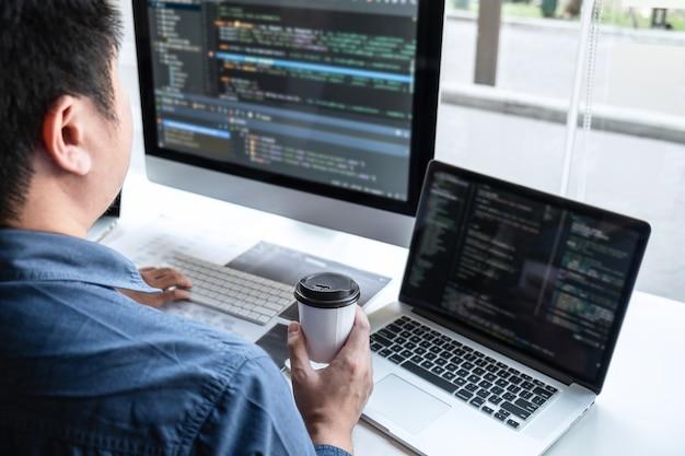 Profesjonalny zespół programistów pracujących nad projektem na komputerze tworzącym oprogramowanie w biurze firmy it, pisaniem kodów i stron internetowych z kodem danych oraz kodowaniem technologii bazodanowych na nowej aplikacji.