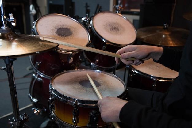 Profesjonalny zestaw perkusyjny zbliżenie. perkusista mężczyzna z pałeczkami grający na bębnach i talerzach, na koncercie rockowym na żywo lub w studiu nagrań