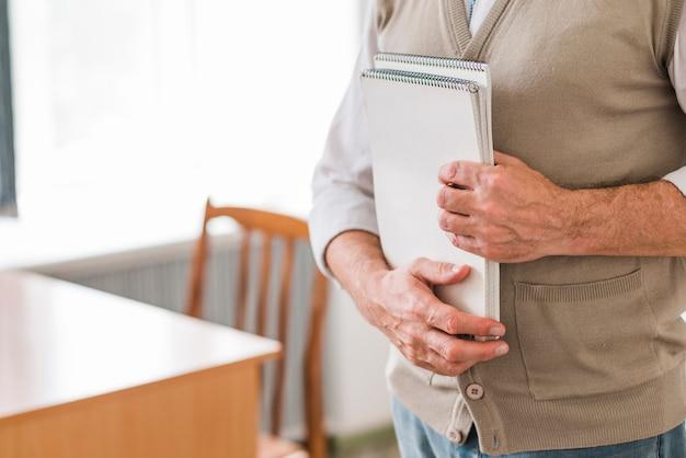 Profesor męski trzyma notatniki w sala lekcyjnej
