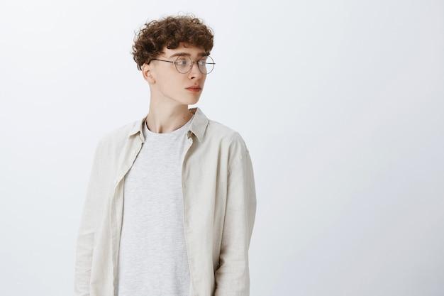 Profil atrakcyjny i stylowy młody facet z kręconymi włosami w okularach patrząc dobrze