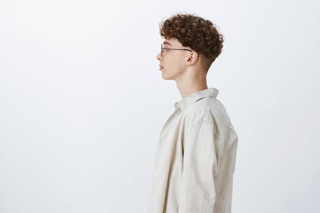 Profil atrakcyjny i stylowy nastoletni facet pozuje na białej ścianie