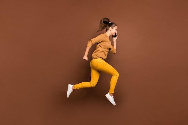 Profil boczny pełnej długości ciała młoda dziewczyna mówiąca przez telefon biegnący w kierunku centrum handlowego z rabatem