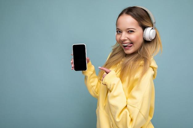 Profil boczny seksowna piękna młoda blondynka na sobie żółtą stylową bluzę z kapturem