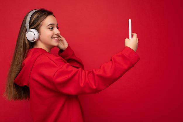 Profil boczny strzał szczęśliwy uśmiechający się ładna brunetka dziewczyna ubrana w czerwoną bluzę z kapturem na białym tle na czerwonym tle