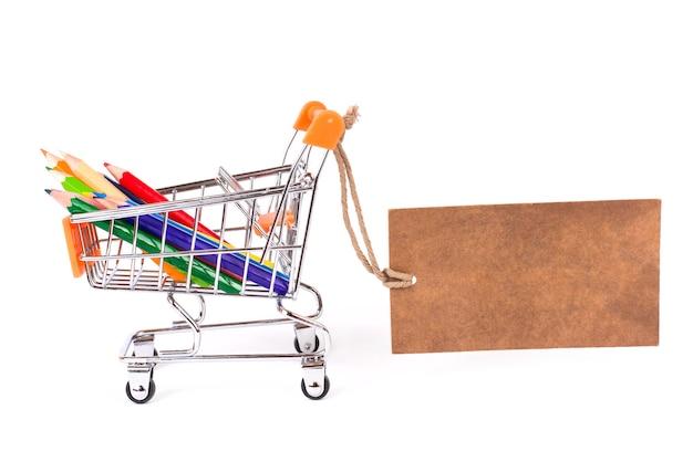 Profil boczny z bliska zdjęcie małego małego wózka z kolorowymi, jasnymi, żywymi ołówkami wewnątrz i latający papier vintage retro brązowy etykieta na białym tle kopia przestrzeń