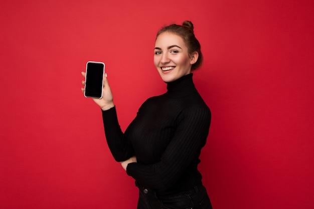 Profil boczny zdjęcie atrakcyjne pozytywne młoda brunetka kobieta ubrana w czarny sweter stojący na białym tle nad czerwonym tle wyświetlono telefon komórkowy z pustym ekranem na makieta patrząc na kamery