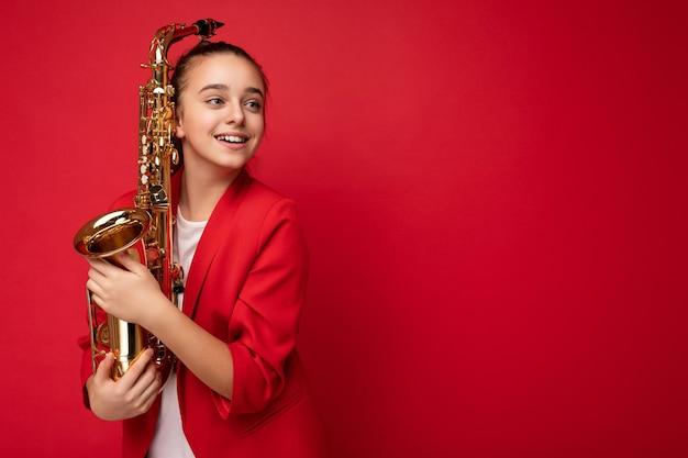 Profil boczny zdjęcie uroczej pozytywnej uśmiechniętej brunetki małej dziewczynki w modnej czerwonej kurtce stojącej na białym tle nad czerwonym tle ściany trzymającej saksofon patrząc z boku