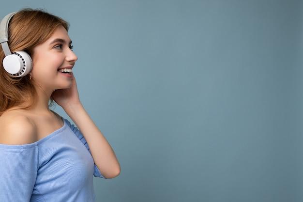 Profil boczny zdjęcie uroczej pozytywnej uśmiechniętej młodej blondynki na sobie niebieski krótki top na białym tle