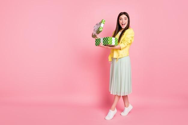 Profil całego ciała śmieszna dama trzyma za ręce duże zielone pudełko upominkowe otwarty prezent
