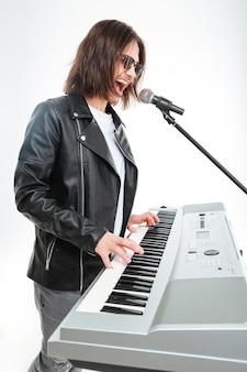 Profil charyzmatycznego młodego mężczyzny z długimi włosami grającego na syntezatorze i śpiewającego w mikrofonie na białym tle