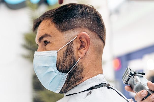 Profil dorosłego mężczyzny rasy kaukaskiej ze świeżo ogolonymi włosami, noszącego maskę w zakładzie fryzjerskim
