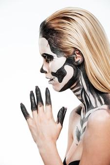 Profil dziewczyny z przerażającym makijażem halloween na białym tle