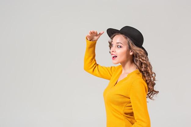 Profil emocjonalnej dziewczyny w kapeluszu na szaro