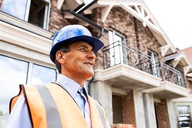 Profil i niski kąt szczęśliwego mężczyzny w kasku i kamizelce pracownik na miejscu inżynier w średnim wieku odwraca wzrok od mężczyzn na budowie i inżynierów