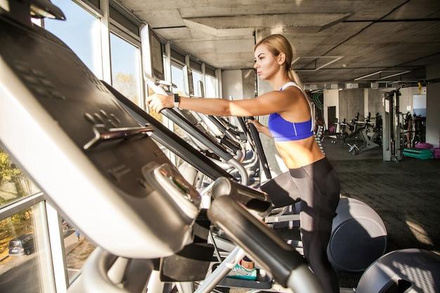 Profil kobiety instruktorki w klubie fitness jeździć na orbitrack