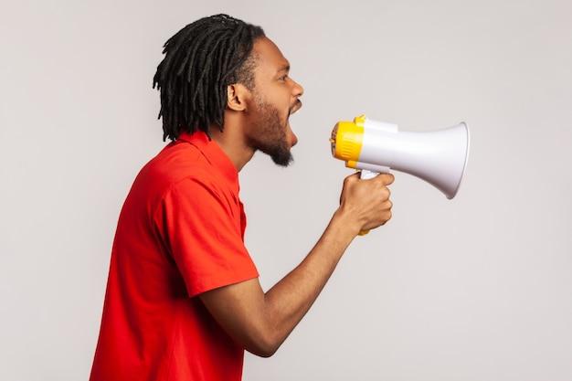Profil mężczyzny głośno krzyczącego do megafonu, protestującego, chce być wysłuchany.