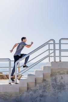 Profil młodego mężczyzny biegnącego po schodach na zewnątrz z czystym niebem w porcie
