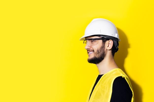 Profil młodego, uśmiechniętego człowieka architekta, inżyniera konstruktora, na sobie biały kask budowlany, okulary i żółtą kurtkę na białym tle na żółtej ścianie.