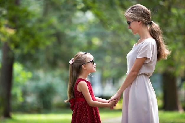 Profil młodej blond długowłosa atrakcyjna uśmiechnięta kobieta i mała dziewczynka w okulary i modne sukienki.