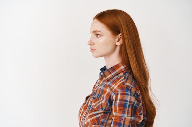 Profil młodej kobiety o długich, zdrowych, rudych włosach i bladej skórze, patrzącej w lewo z poważną twarzą, stojącej nad białą ścianą