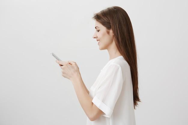 Profil młodej ładnej kobiety sms-y, przy użyciu telefonu komórkowego, zamówienie online
