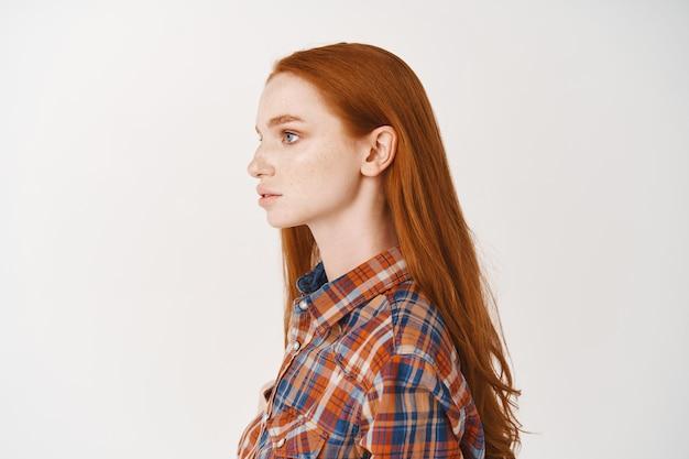 Profil młodej rudowłosej studentki z długimi naturalnymi rudymi włosami i bladą skórą, patrzącą w lewo, stojącą w luźnej koszuli na białej ścianie