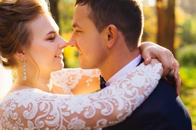 Profil nowożeńców panna młoda i pan młody obejmują się i patrzą na siebie w parku