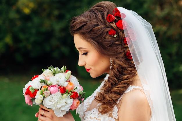 Profil panny młodej z elegancką fryzurą trzyma bukiet ślubny