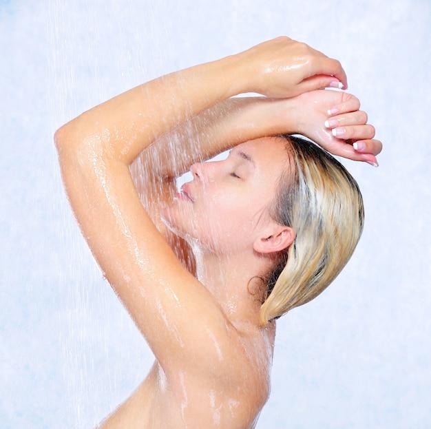 Profil piękna młoda dziewczyna pod prysznicem