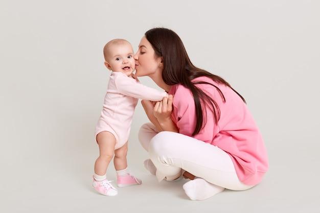 Profil pięknej kobiety z długimi włosami siedzi na podłodze ze skrzyżowanymi nogami i całuje jej małą córeczkę stojącą obok niej, matka trzyma niemowlę z rękami odizolowanymi na białej ścianie.