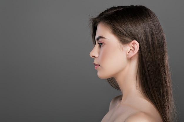 Profil pięknej młodej kobiety o doskonałej skórze i naturalnym makijażu. kopiuj przestrzeń