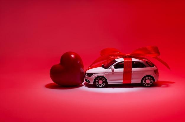 Profil po stronie bliska widok zdjęcia pięknej białej zabawki nowoczesny modny modny samochód z czerwoną wstążką i kokardą czerwone serce w centrum w reflektorze reflektora na białym tle na czerwonym tle
