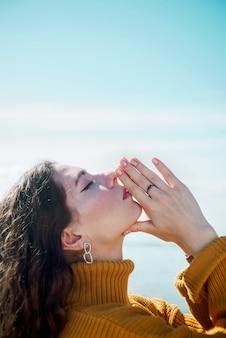 Profil portret młodej dorosłej białej kobiety z zamkniętymi oczami robi namaste gest i dotyka jej