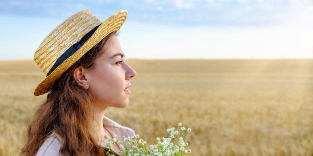 Profil portret młodej kobiety w słomkowym kapeluszu iz bukietem dzikich kwiatów w polu pszenicy o świcie