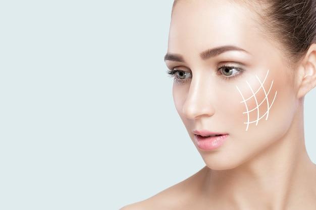 Profil portret pięknej kobiety na szarym tle zbliżenie. kobieta ze strzałkami na twarzy