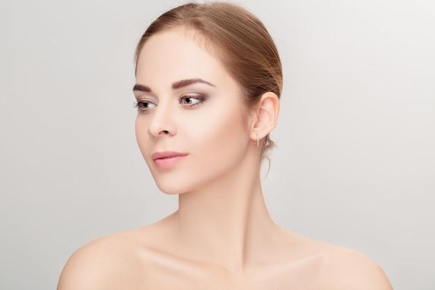 Profil portret pięknej młodej kobiety blondynka z zielonymi oczami na szarym tle zbliżenie. dziewczyna z czystą skórą