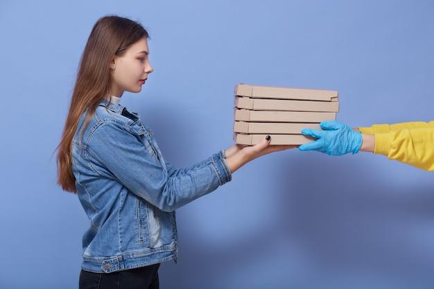 Profil poważnej spokojnej młodej modelki z długimi włosami, która dostaje paczkę od kuriera, ręce w rękawiczkach daje kilka kartonów z jedzeniem dla klienta, usługi online, dostawa żywności podczas kwarantanny.
