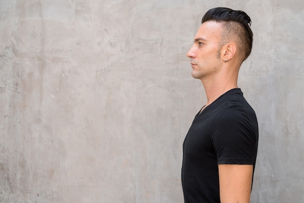 Profil przystojny młody człowiek jest ubranym czarną koszulkę z podcięciem