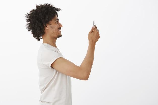 Profil przystojny murzyn robi zdjęcie czegoś na smartfonie, fotografuje w telefonie